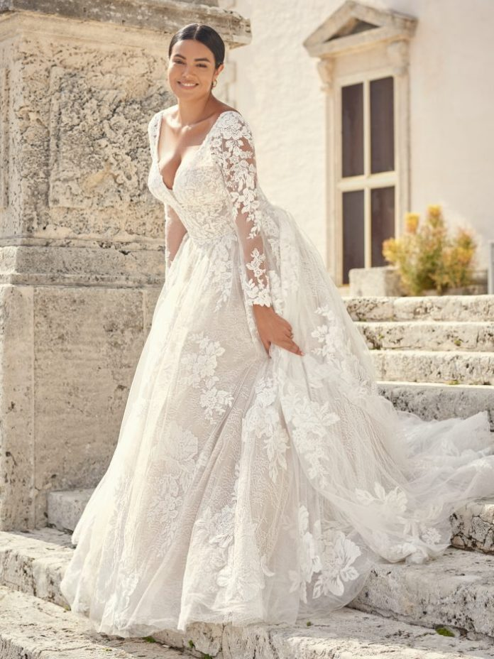 Bride wears a long-sleeved wedding dress with floral lace called Valona by Sottero and Midgley