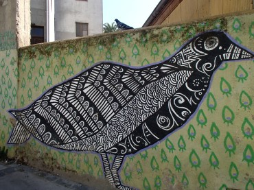 Artsy graffiti of a bird with a pigeon above in Valparaiso