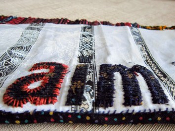 'Aim' affirmation in cloth font, hand embroidered onto stripy fabric ground.