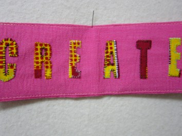 a shocking pink oyster card wallet with an affirmation 'create' in bright yellow and red hand stitched upon it.