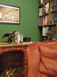Chimenea con libros y sofá rojo en el día internacional de leer a Tolkien
