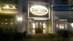 A large lighted, wooden sign and two dark wood entry doors serve as the entry to Trattoria al Forno
