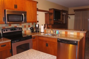 View of kitchen including stainless steel range, dishwasher, microwave