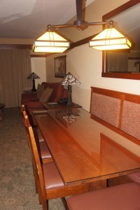View of dining table with banquette seating and four chairs and couch in living room