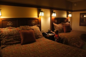 Two queen beds featuring Arts & Crafts style furniture and art glass sconces
