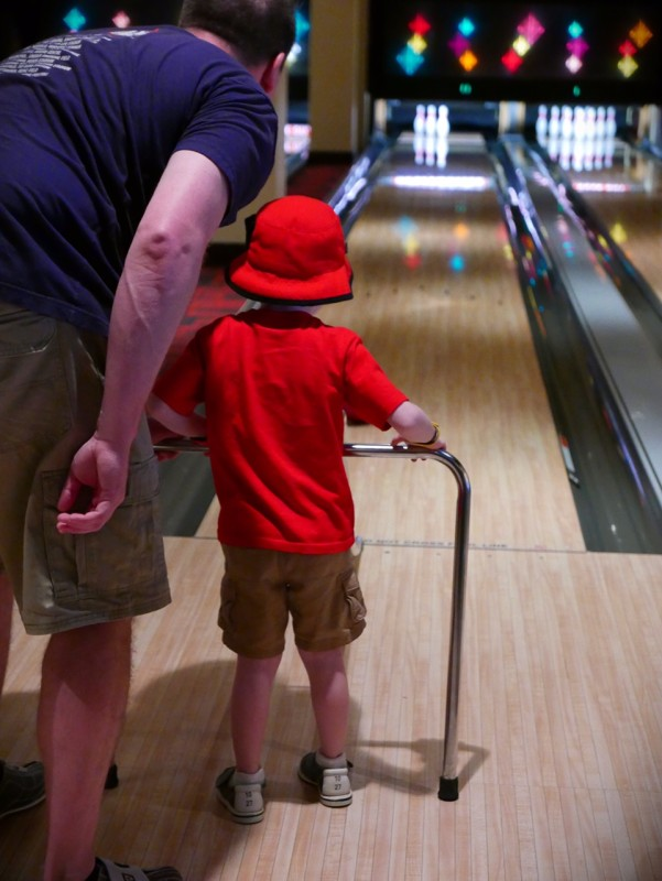 Dad helps son bowl rear view