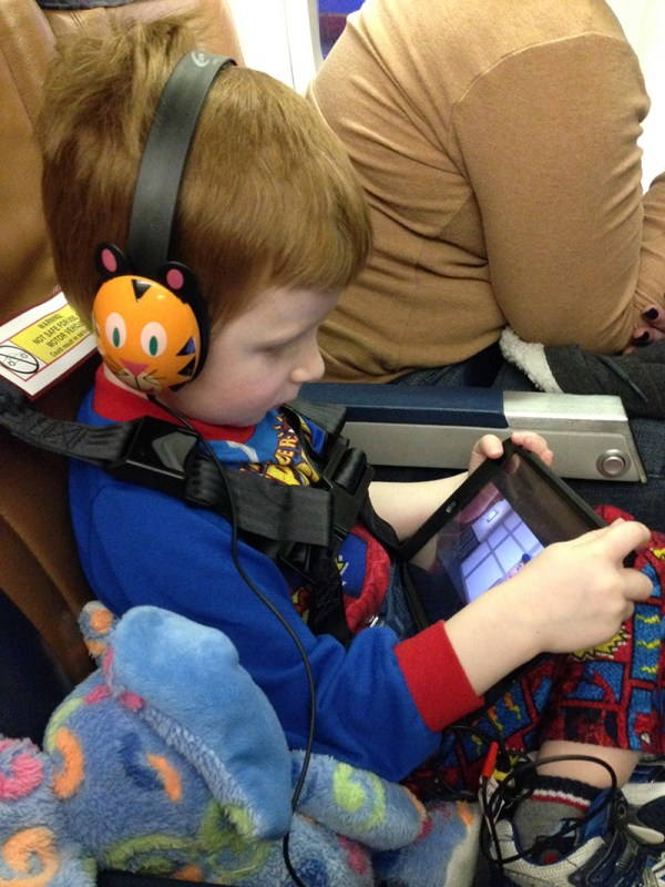 A boy is seated wearing the CARES harness and snazzy headphones.