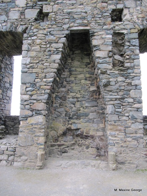 The remains of a fireplace in the former Great Hall at Harlech Castle. Little survives of the range of buildings located along the northern side of the courtyard. The ruins of the chapel walls are the most prominent feature there.