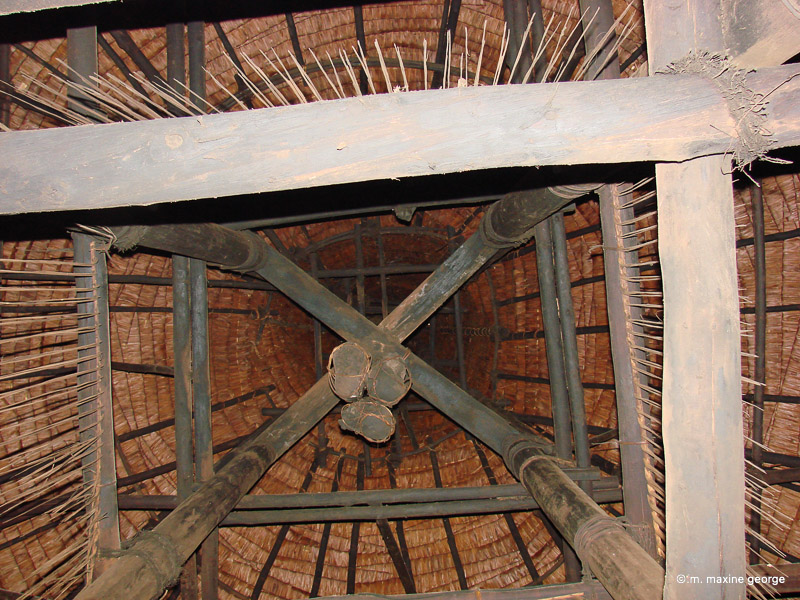 Skulls hang from the peak of the thatched roof in what might have once been home of a head-hunter! Photo by M. Maxine George