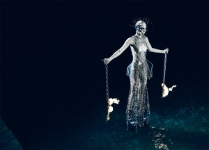 Model holding chains on fire and a metal dress