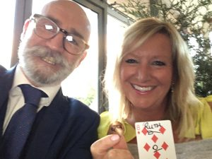 Woman holding a playing card and a bent soin. Accompmnaied by a magician. Magic Frank