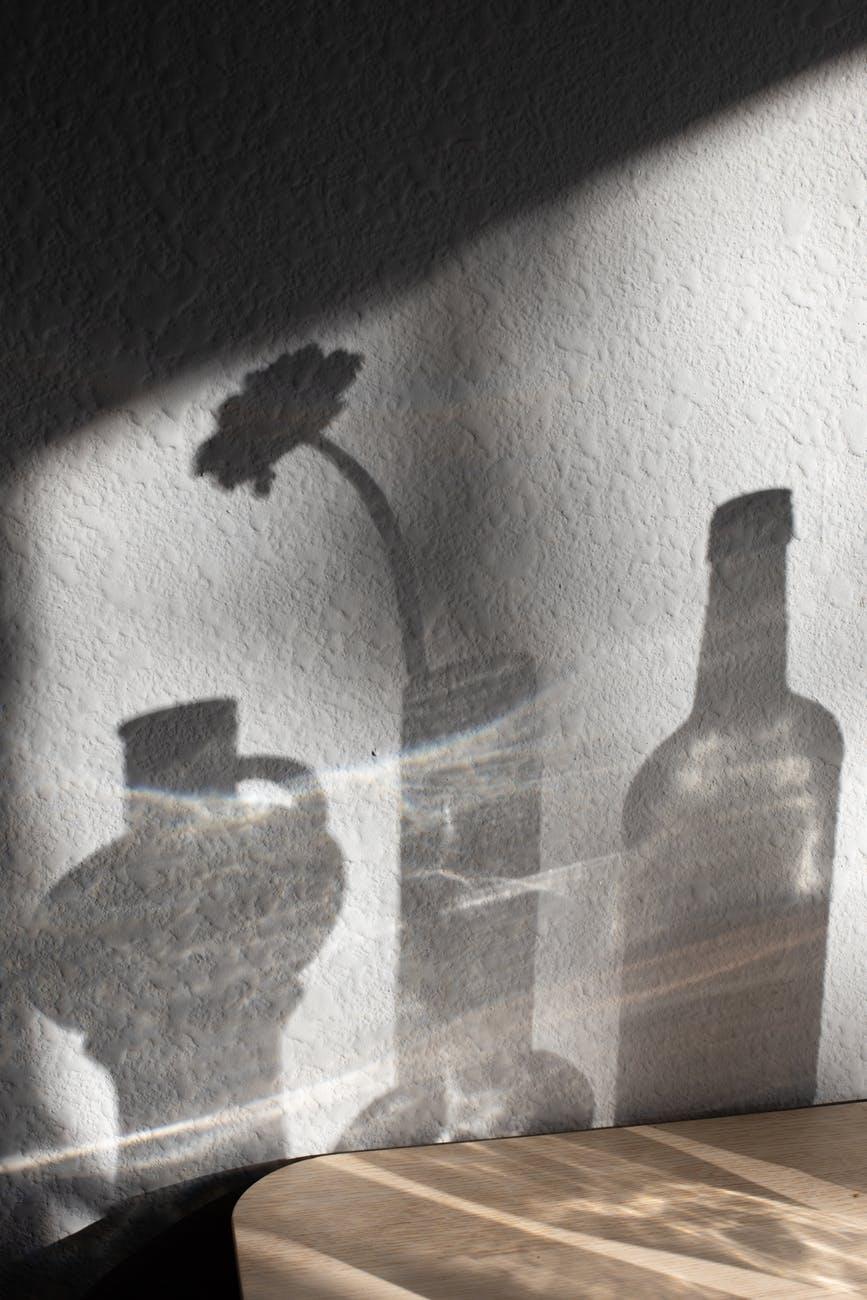 bottle and jug arranged with vase of flower