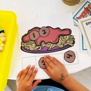 Student using a breathing and counting mat by placing numbered meatballs on an image of a plate of spaghetti
