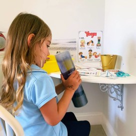 Child playing with bottle while cooling off in the calm down corner.