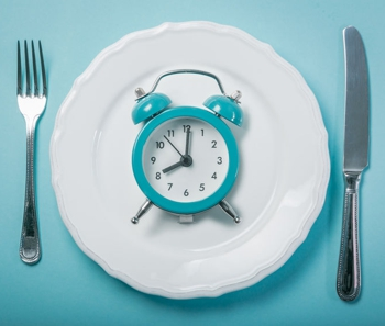 a clock on a plate intermittent fasting