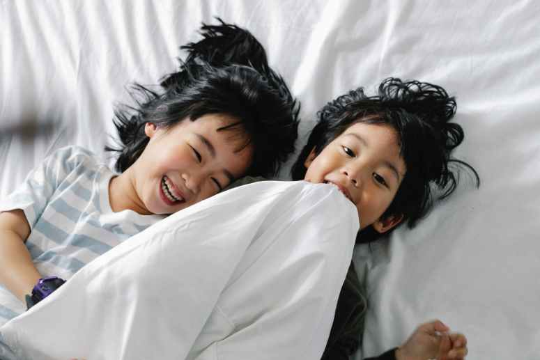 kids lying on white bed