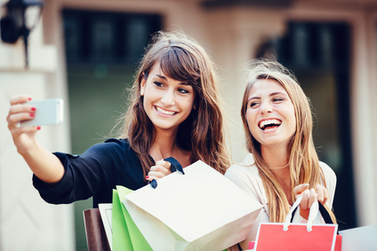 """Two young women shopping at the mall taking a """"selfie"""" or self portrait with their cell phone"""
