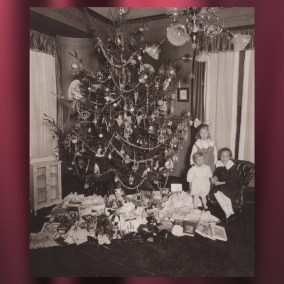 Here, members of the Wilson family – Clara Louise, Marjorie, and Ernie Jr. – pose by the family Christmas tree in 1917.  <br><br>Gift of Clara Louise Schafer, 2019.12