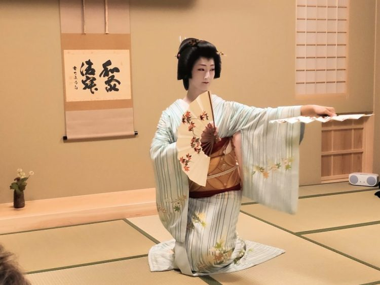 Geiko dancing with hand fans at Maikoya