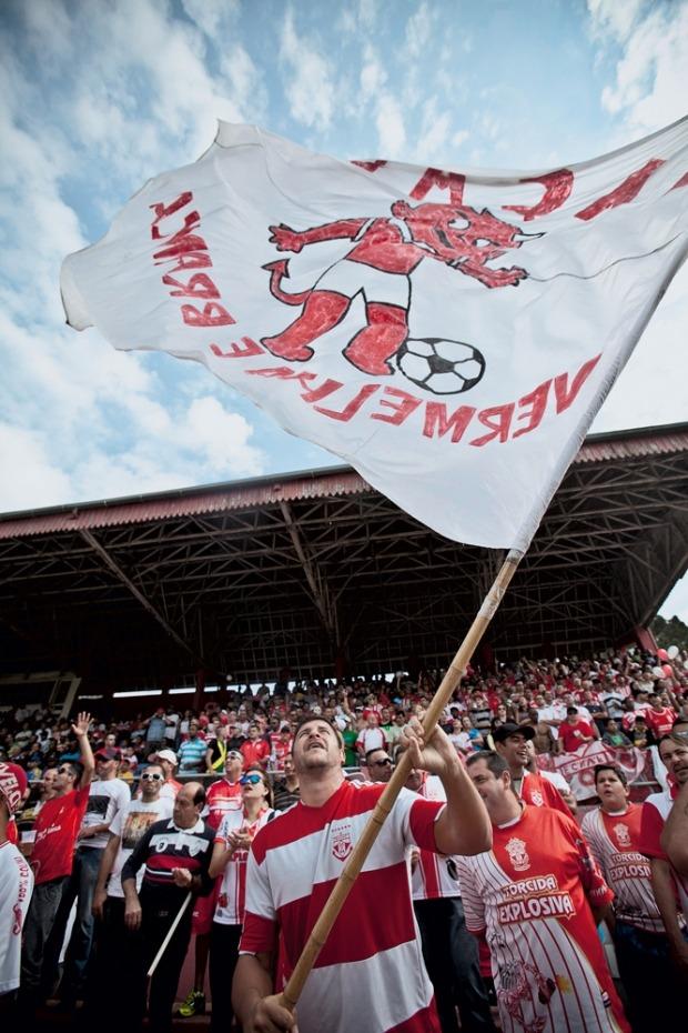 No alto, a bandeira no estádio, que na várzea é permitida