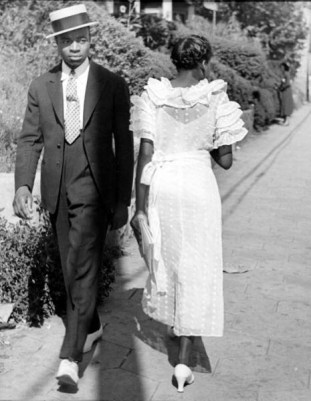 Young African-American gentleman sporting his Sunday finery glancing at a frilly-frocked girl passing him on the street. Photograph by Alfred Eisenstaedt. Mississippi, USA, 1937.