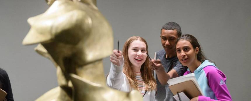 Three teens, a boy and two girls, pointing at a sculpture with notebooks and pencils