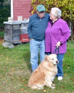 Pictured in front of some of their bee hives with their dog Honey, Dick and Jean Vose, of Nobleboro, were given the Maine State Beekeepers Association's 2014 Beekeeper of the Year award Oct. 18. (D. Lobkowicz photo)