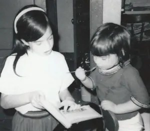 A girl of about 8 reads a book to a girl of about 3 or 4.