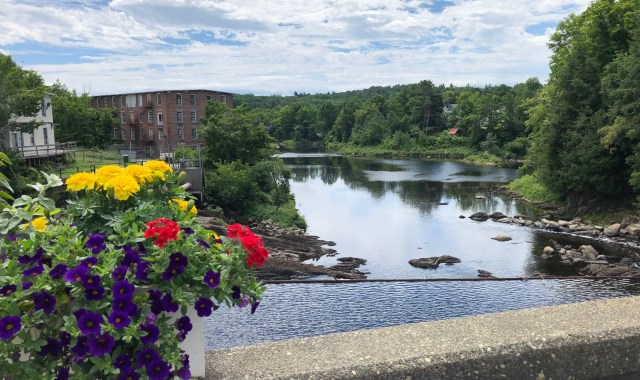 A view of a pretty river from a bridge with a pot of flowers ont he railing