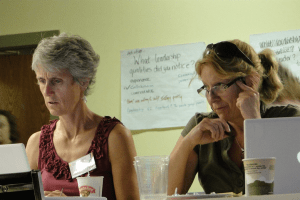 Two art teachers share materials at the four-day Maine Arts Assessment Initiative institute in August.