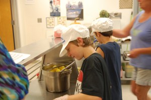 Brooklin students in grades 4 through 8 are on a rotating schedule to help cook Lori Boyce in the kitchen. Last Thursday, Colby Schneider served broccoli to students, and Lucas Torrey dished up corn.