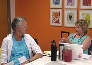 Visual art teachers Debi Lynne Baker (left) and Jane Snider discuss proficiency and standards at the MAAI summer institute at Maine College of Art.
