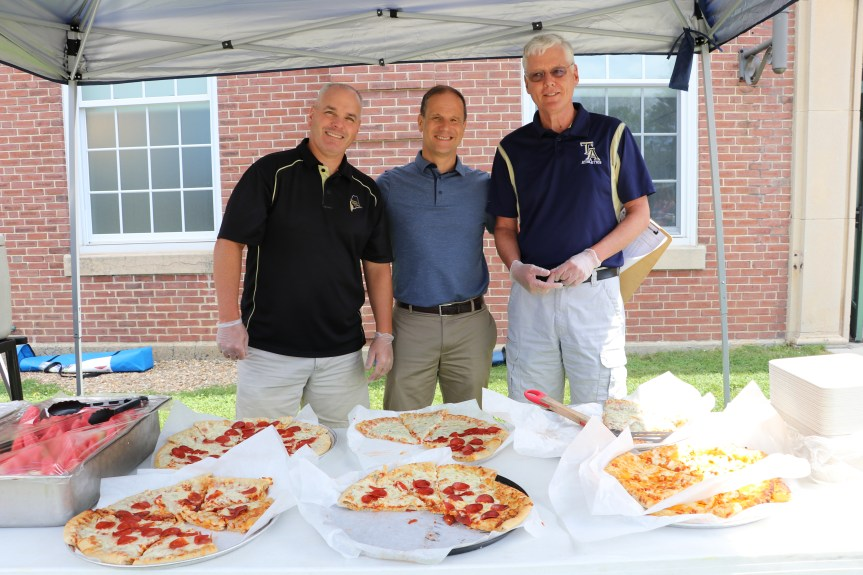 Traip Academy Assistant Principal/Athletic Director, Kittery School Department Superintendent, Eric Waddell, and Michael Roberge, Traip Academy Principal John Drisko serving pizza at the event
