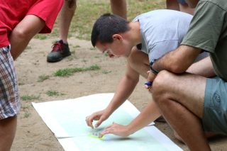 A student shows the class how to locate their position on the map