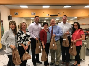 School Administrators holding shopping bags of food.