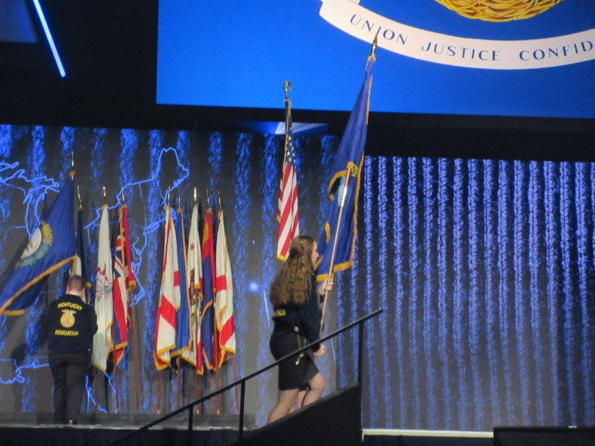 Maine FFA State Secretary-Treasurer Ava Cameron presents the Maine Flag at the Opening Session.