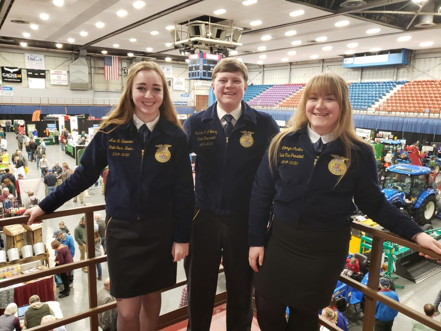 Maine FFA State Officers Ava Cameron (Secretary-Treasurer), Graham Berry (President) and Camryn Curtis (Vice President) stand above the many agricultural organization displays for the 2020 Maine Agricultural Trades Show