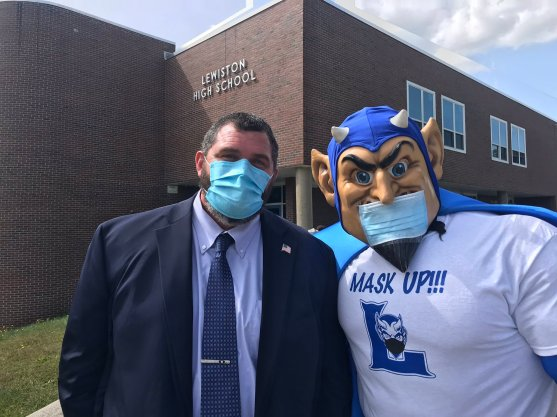 Superintendent and mascot pictured wearing masks outside Lewiston High School