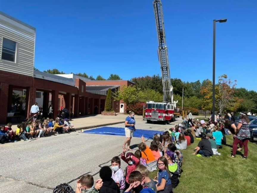 Fire truck with latter up. students gathered outdoors watching