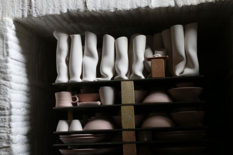 A Bisque Kiln containing bowls, mugs, and many twist vases.
