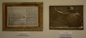 The framed print on the left is an original 1906 print of the USS Maine. The bronze plaque on the right was cast in 1913 from original pieces of metal taken off the USS Maine when she was taken out of the harbor in Havana into deep water and sunk. There were only 1000 castings of which fewer than 50 are known to exist today.