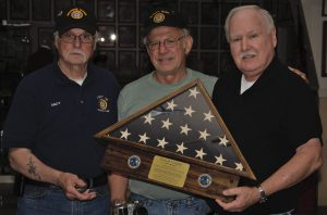 (L to R) Andy Buckman, Head Fundraiser, and Ron Vigue, Past Post Commander, of American Legion Post 79 of Berwick, Maine present Curator Lee Humiston with the flag honoring Ernest Valatie of Bangor, Maine, killed in action in Korea in 1949.