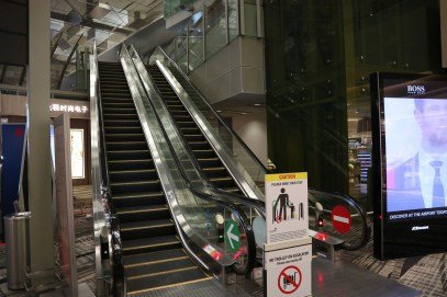 Escalator to mezzanine, turn left after immigration (Photo: Mainly Miles)