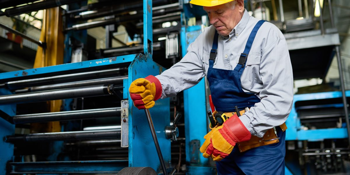 Portrait of senior factory worker switching levers on big machines in workshop