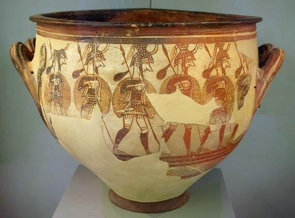 Zes Mykeense krijgers trekken ten strijde; links worden ze door een vrouw uitgezwaaid. Deze pot is gevonden in Mykene en nu in het Nationaal Archeologisch Museum in Athene.