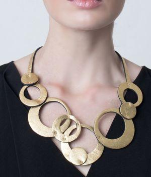 Collar de círculos de cuero dorado sobre modelo. Olivia Corto, Maison Domecq