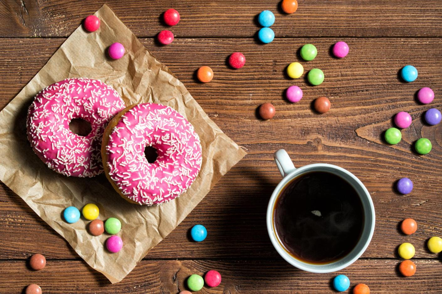 Two pink donuts and coffee on wooden table