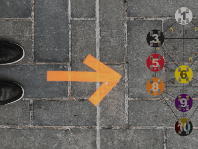Feet on a cobbled street standing behind an arrow pointing to a Qabala glyph