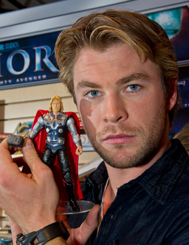Thor movie lead Chris Hemsworth holds his action figure at Hasbro's Toy Fair showroom in New York