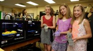 Three middle school girls hold e-NABLE hands next to a makerbot printing a hand
